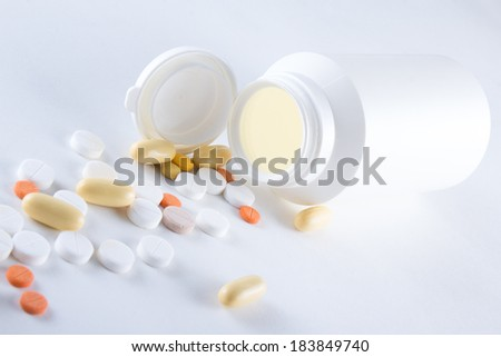 close up of colorful capsules pouring from plastic bottle over white background