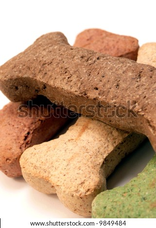 Close up of colorful dog treats over a white background