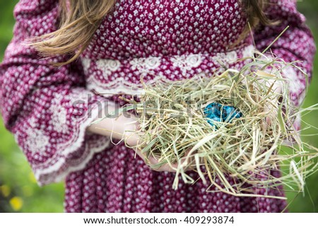Close up of colorful Easter eggs in a nest in the hands of women