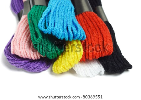 Close up of colorful embroidery threads on white background