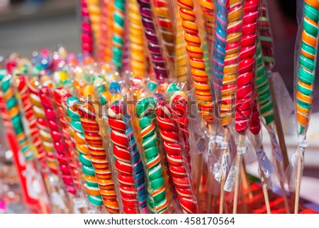 Close up of colorful handmade swirl lollipops on street market  - stock photo