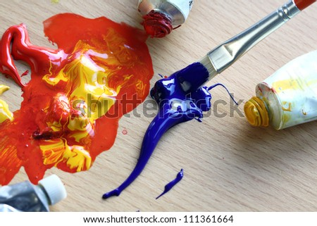 Close up of colorful paint and brush. Focus in the brush - stock photo