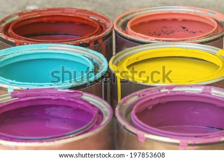 Close up of colorful paint in cans buckets tins - stock photo