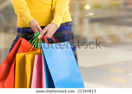 Close-up of colorful paperbags being held by female in the shopping center