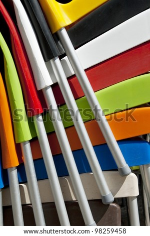 Close up of colorful plastic chairs stacked in a column. Useful  for decorative background