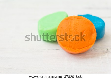 close up of colorful playdough on wooden table. - stock photo