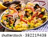 Close Up of Colorful Spanish Seafood Paella Dish with Langostina and Shellfish Served in Shallow Pan with Red Handles on Rustic Wooden Table with Fresh Lemon Garnish in Background - stock photo
