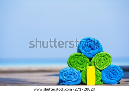 Close up of colorful towels and sunscreen bottle background the sea - stock photo