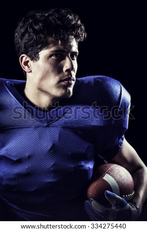 Close-up of confident American football player looking away against black