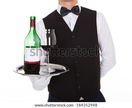 Close-up of confident young waiter holding tray with glass of red wine and bottle against white background - stock photo
