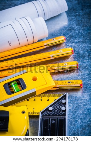 Close up of construction level blueprints and measurement tools on metallic scratched surface building and architecture concept. - stock photo