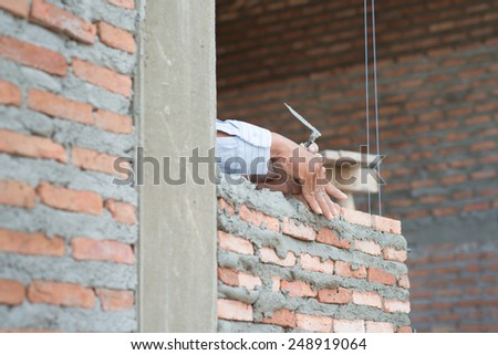 Close-up of construction process mason work with brick installation. - stock photo