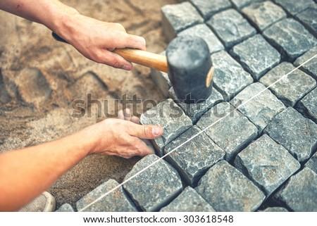 Close-up of construction worker installing and laying pavement stones on terrace, road or sidewalk. Worker using stones and rubber hammer to build stone sidewalk - stock photo