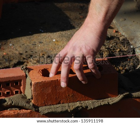 Close up of construction worker's hand pressing brick into place. - stock photo
