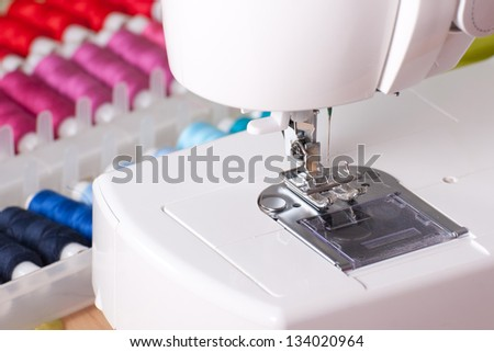 Close-up of contemporary sewing machine with colored spool box. - stock photo
