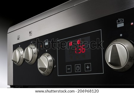 Close up of controls from a modern stainless steel oven with timer. - stock photo