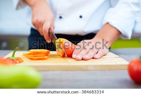 Close-up of cook chopping bell pepper