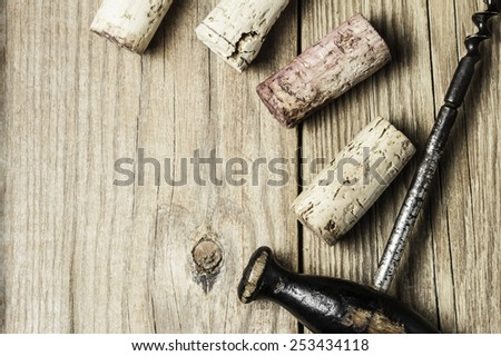 Close-up of corks and  a corkscrew on a wooden  background