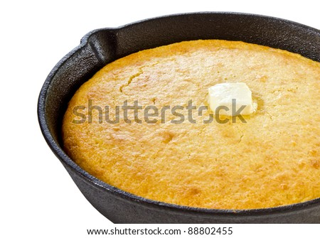 Close up of cornbread in iron skillet isolated on white - stock photo