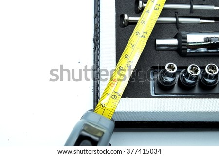 Close up of corner of tool box with screwdriver, adjustable torque, steel tape measure. Isolated on white. Space for texts. - stock photo
