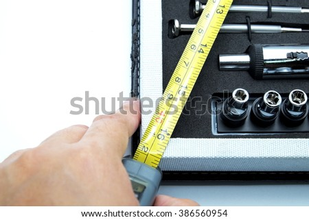Close up of corner of tool box with screwdriver, adjustable torque, steel tape measure with hand. Isolated on white. Space for texts. - stock photo
