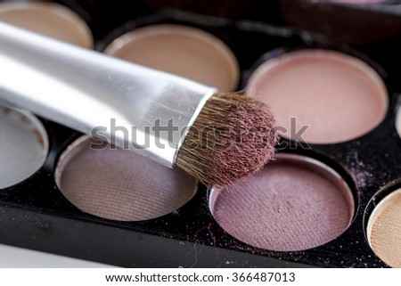 Close up of cosmetic brush with mauve eye shadow dust sitting on top of palette of nude eye shadow shades