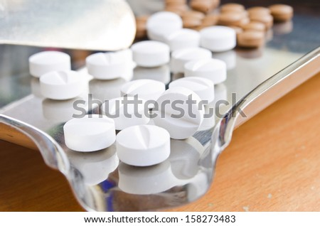 Close up of Counting tablets medical pills on stainless steel tray.(Health care and medical concept)