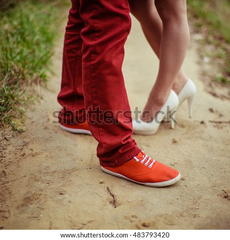 Close-up of couple feet in red and white shoes