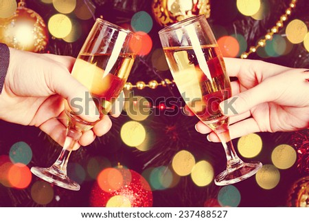 Close up of couple hands holding glasses of champagne over Christmas tree with lights