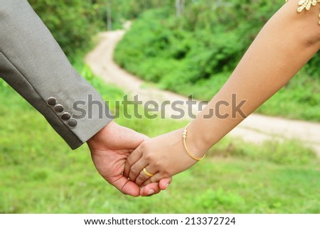Close up of couple holding hands - stock photo