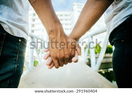 Close up of couple holding hands. - stock photo
