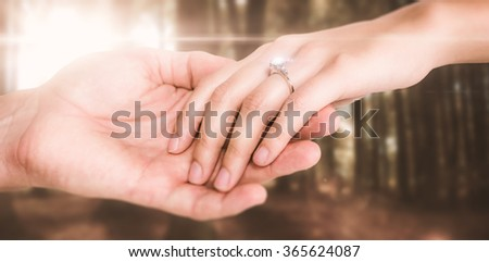 Close-up of couple holding hands against autumn scene