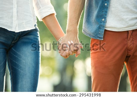 Close up of couple holding hands over sunny and nature