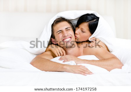 Close up of couple playing in bed. Covered with blanket woman lying on the back of the man kisses him