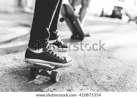 Close up of couple riding skateboards. Woman standing on penny board, man riding skateboard. Black and white photo. Depth of field, selective focus - stock photo