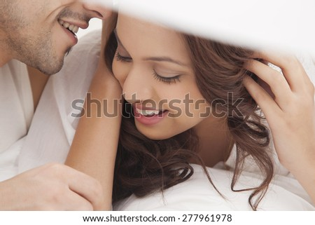 Close-up of couple romancing in bed - stock photo