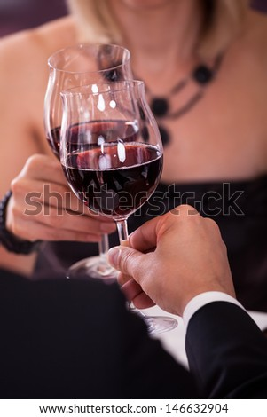 Close-up Of Couple's Hand Holding Red Wine And Toasting Glass - stock photo
