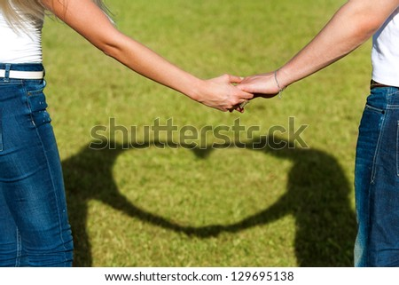 Close up of couples hands together with shadow of heart sign. - stock photo