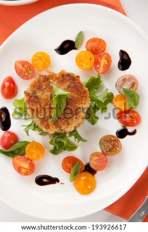Close up of crab cakes and cherry tomato salad appetizer garnished with basil, and balsamic vinegar sauce.