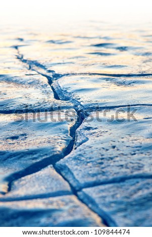 Close up of crack in ice on lake in early spring - stock photo