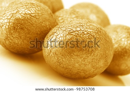 Close-up of crackle golden Easter eggs on white background. - stock photo