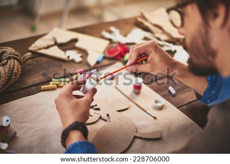 Close-up of craftsman painting xmas symbols with white gouache - stock photo