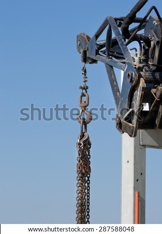 Close up of crane hook and chains against blue sky with concrete skeleton in background - stock photo