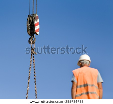 Close up of crane hook lifting weights against blue sky, worker blurred in forefront - stock photo