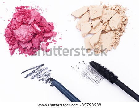 Close up of crashed cosmetics with black pencil and mascara on white background - stock photo
