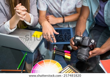 Close up of creative business people with digital camera at office desk - stock photo