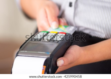 Close up of credit card machine, nice woman hands holding this - stock photo