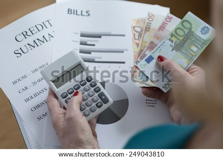 Close-up of credit summary and money counting - stock photo