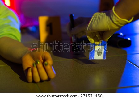 Close-up of crime scene investigator collecting evidence - stock photo