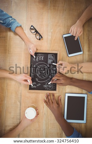 Close-up of cropped hands writing business terms on slate with person touching digital tablet at table - stock photo
